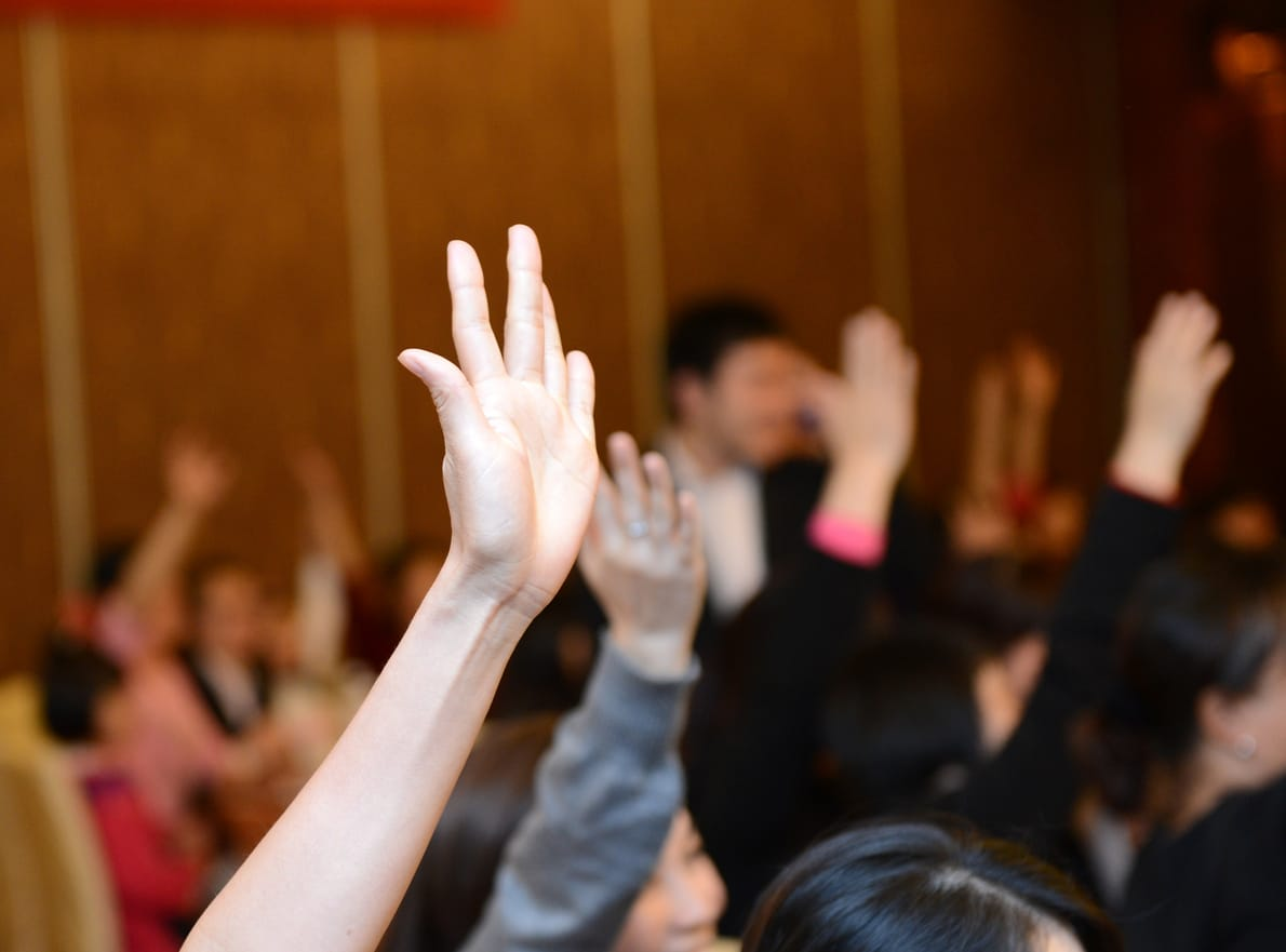 someone raising hand at meeting