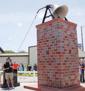 Kenesaw volunteer fire and rescue crewman J.R. Pulver rings the bell topping the Kenesaw Volunteer Fire and Rescue Memorial during the memorial's dedication ceremony Monday. Photo taken by Laura Bernero, Hastings Tribune